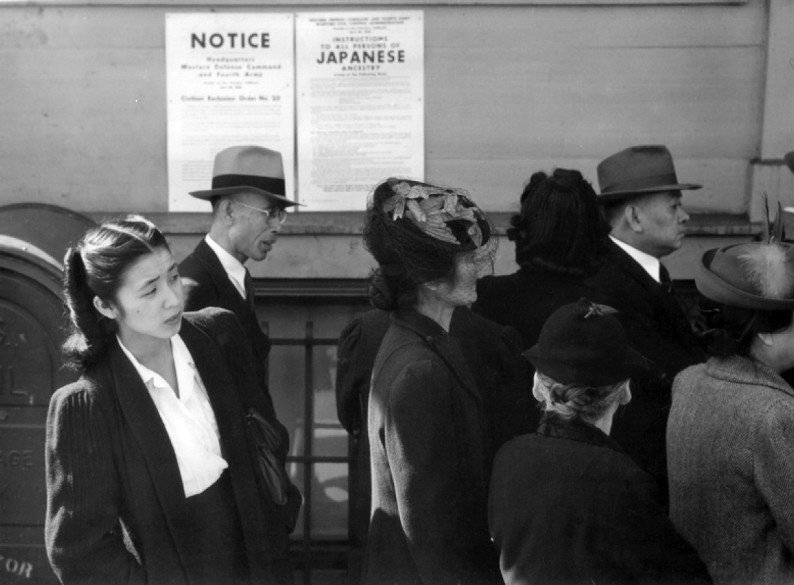 A black-and-white photograph of Japanese Americans in front of notices about the internment order