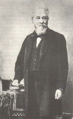 Norbert Rillieux, standing by a table, wearing a dark suit.
