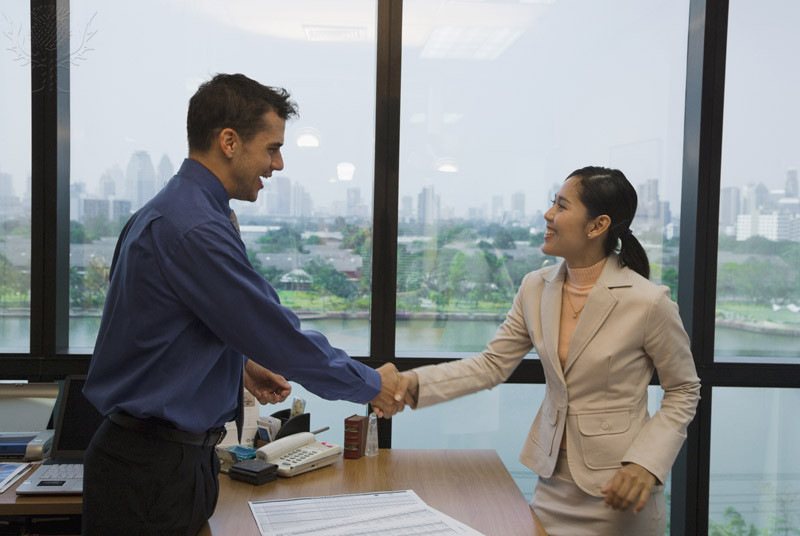 Man and woman shaking hands in an office setting