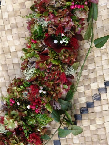 A haku lei of red flowers and greens placed on a lauhala mat