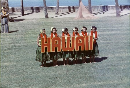Hula dancers holding letters spelling HAWAII