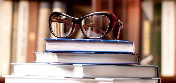 A stack of books with glasses on top