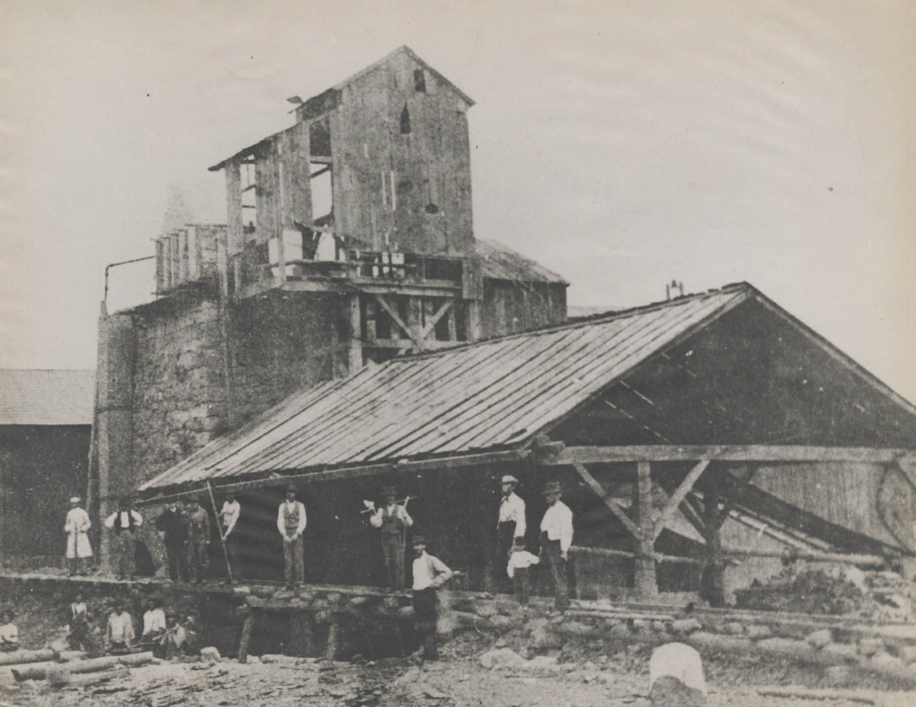 Workmen standing and seated along wooden structure of iron furnace.