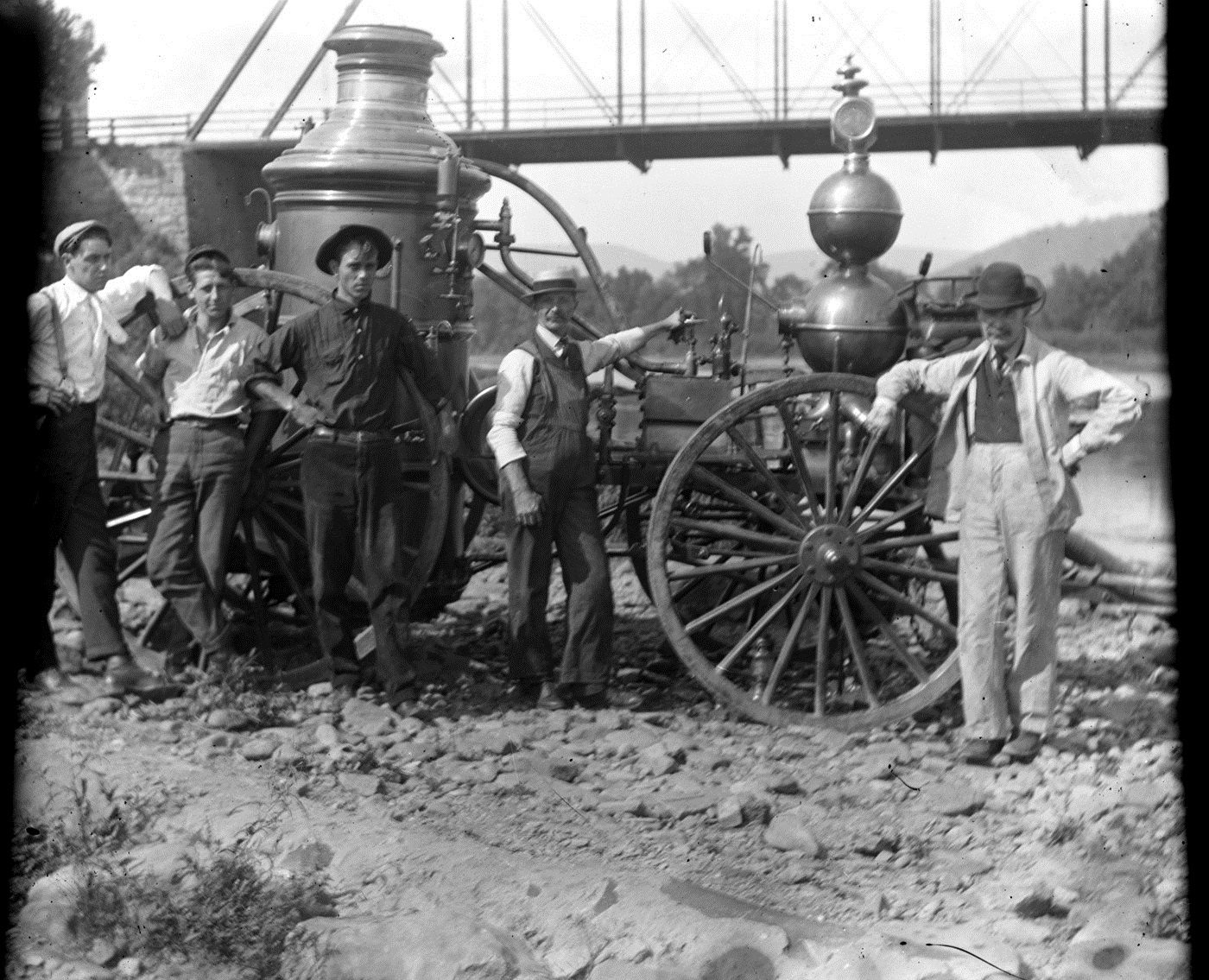 Five men standing alongside a turn-of-the-century (circa 1905-1910) spoked wheel, steam driven fire wagon.
