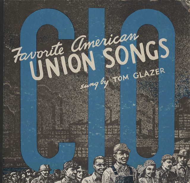 album cover depicting workers marching with factory in the background
