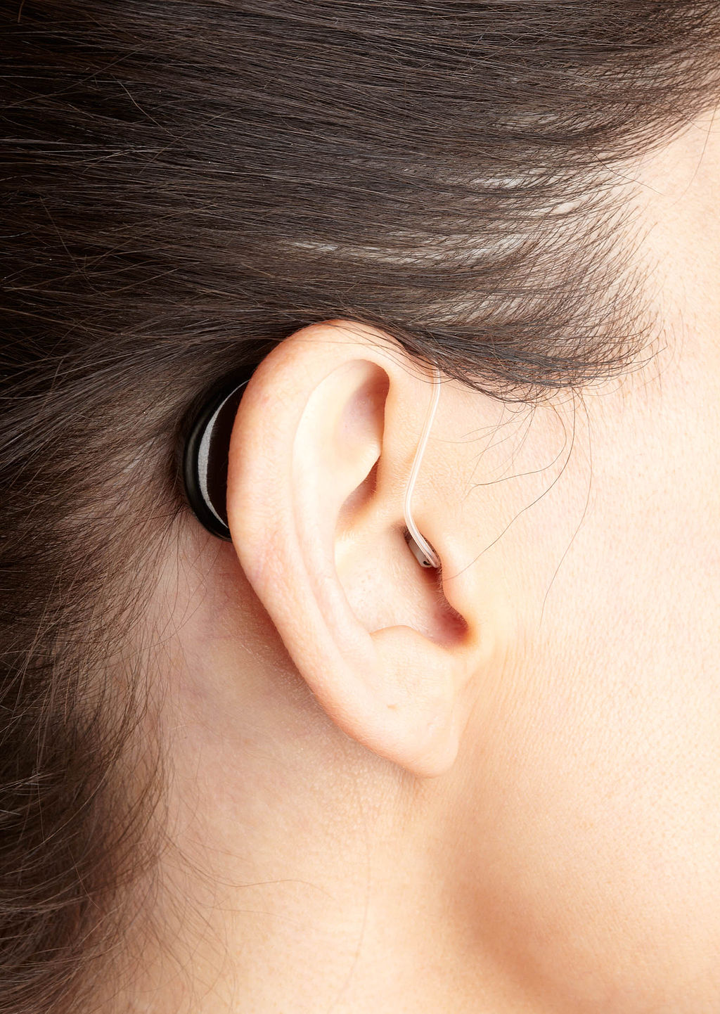 A close up of someone with brown hair wearing a hearing aid