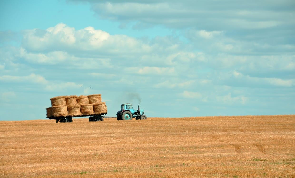 An image of a tractor pulling hay bails in a field