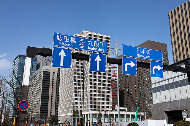decorative image of street signs in Tokyo's business district.