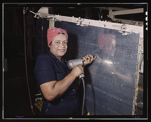 "An African American women operating a hand drill at Vultee-Nashville is working on a ""Vengeance"" dive bomber. Tennessee, 1939."
