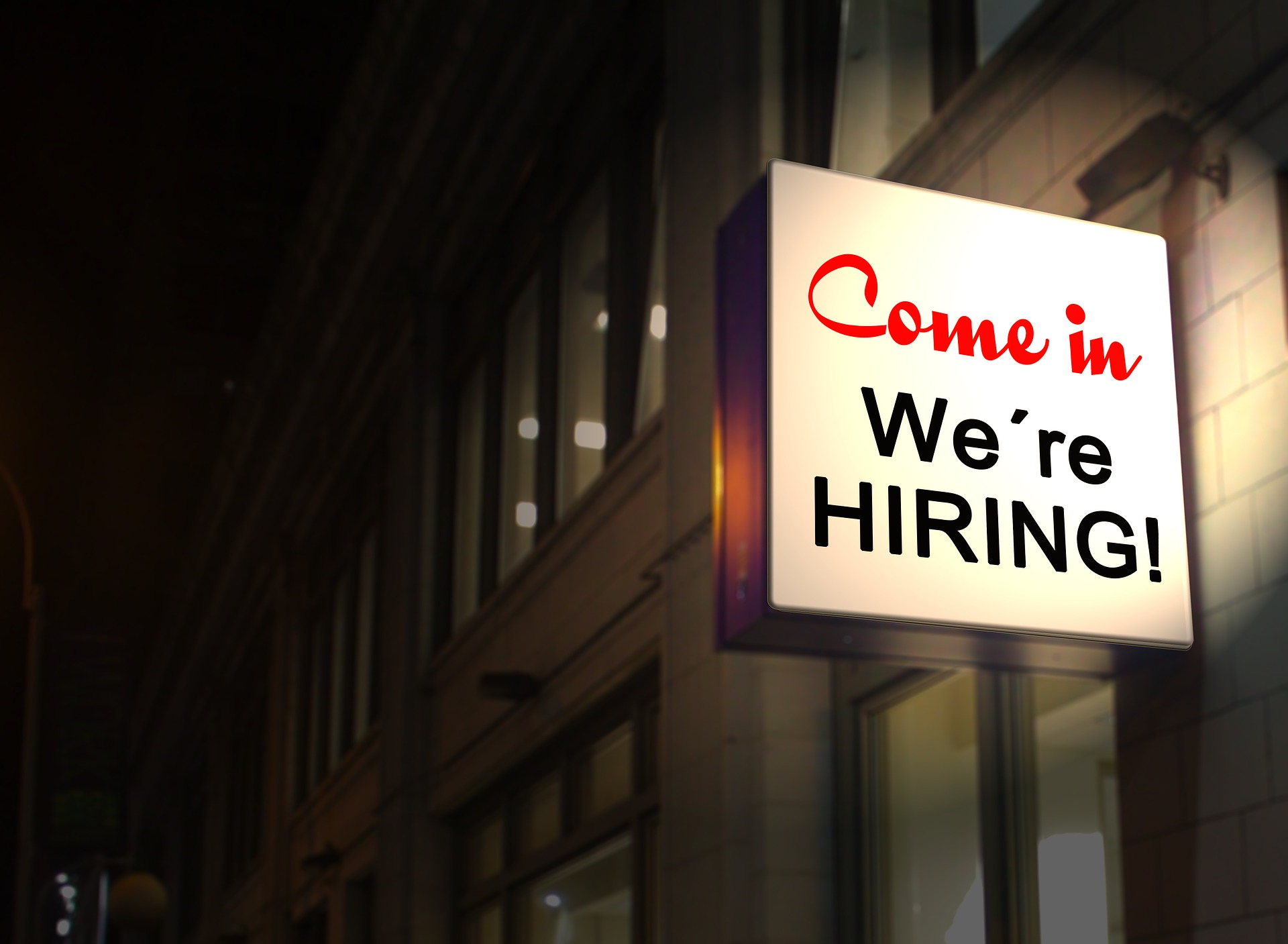 Image stock photo of storefront sign reading come in, we're hiring