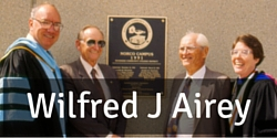 Image link to a page about Wilfred J Airey. Image is of Wilfred J Airey in front of the deadication plaque on the library building.