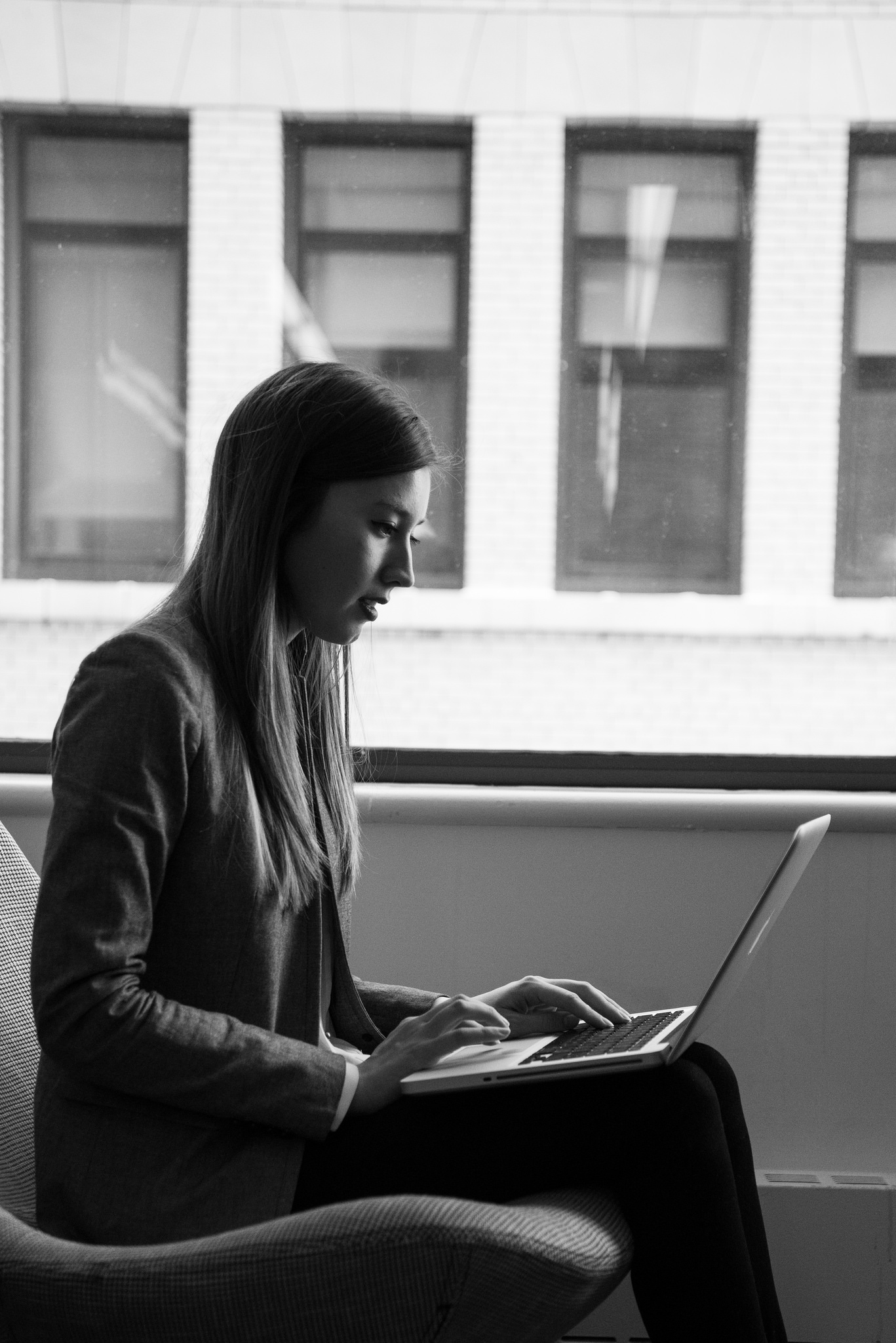 Image of a woman seated with laptop next to a window.