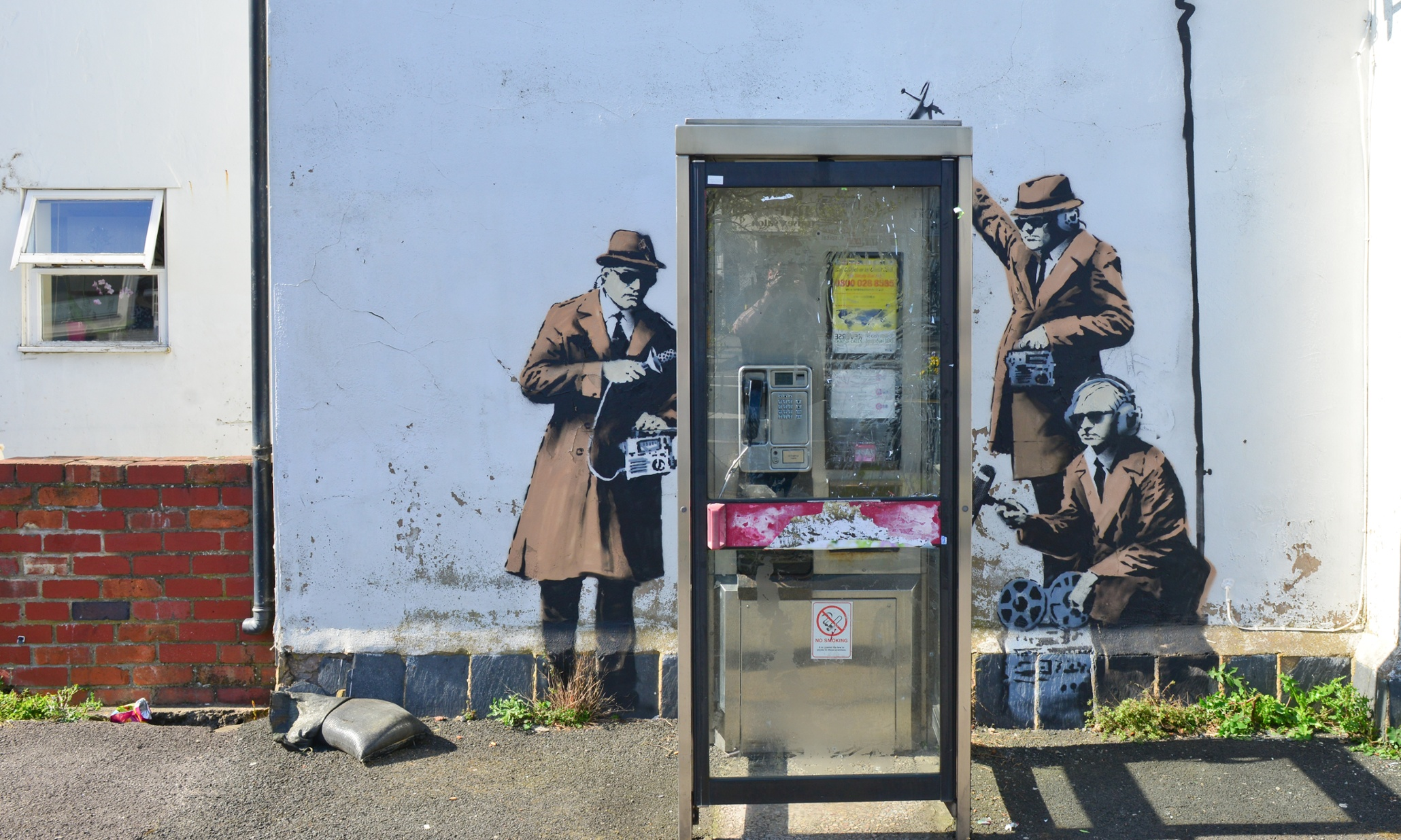 painted mural depicting agents listening in on a phone box