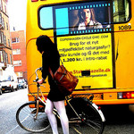 Woman with bike behind bus