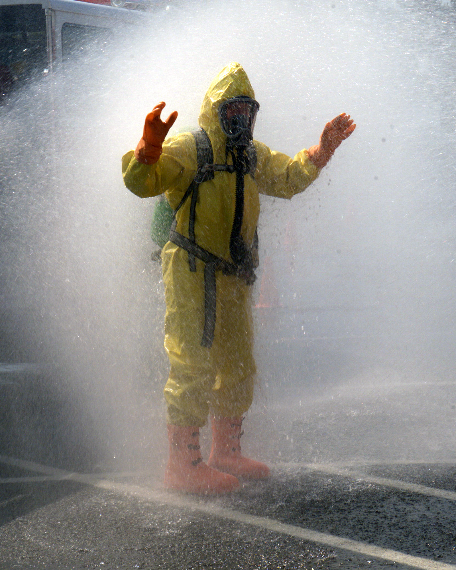 Person in a hazmat suit getting hosed down