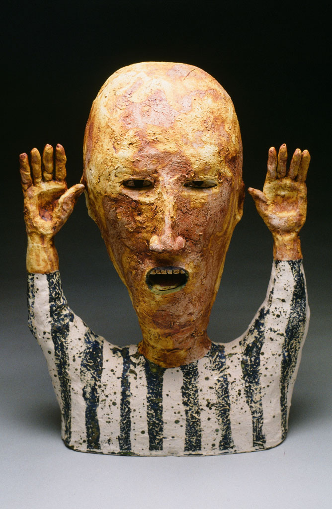 Ceramic figure with raised hands wearing a striped shirt