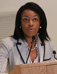 Photo of Monique Akassi (African American woman with shoulder-length hair) speaking at a podium.