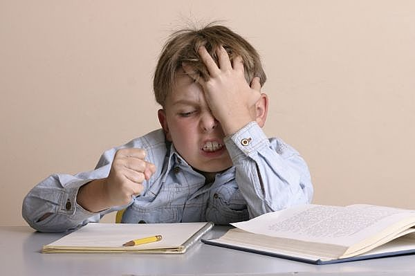 Image of a frustrated child refusing to do his homework
