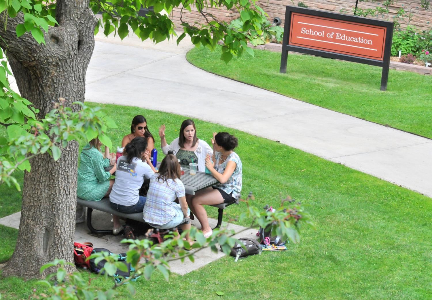 Students socialize outside the School of Education building.