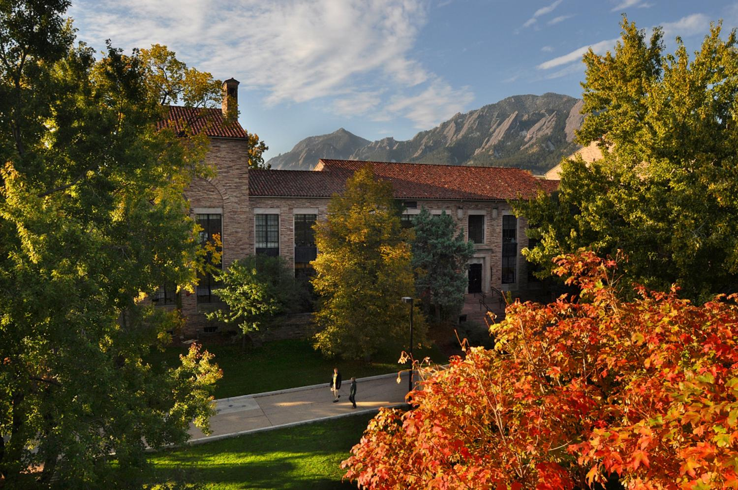 Students stroll by Hellems Arts and Sciences building on an autumn morning at the University of Colorado at Boulder with the majestic Flatirons in the distance.
