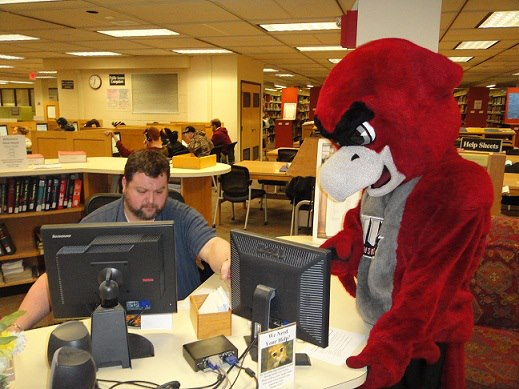 Librarian helping Crimson Hawk mascot at reference desk.