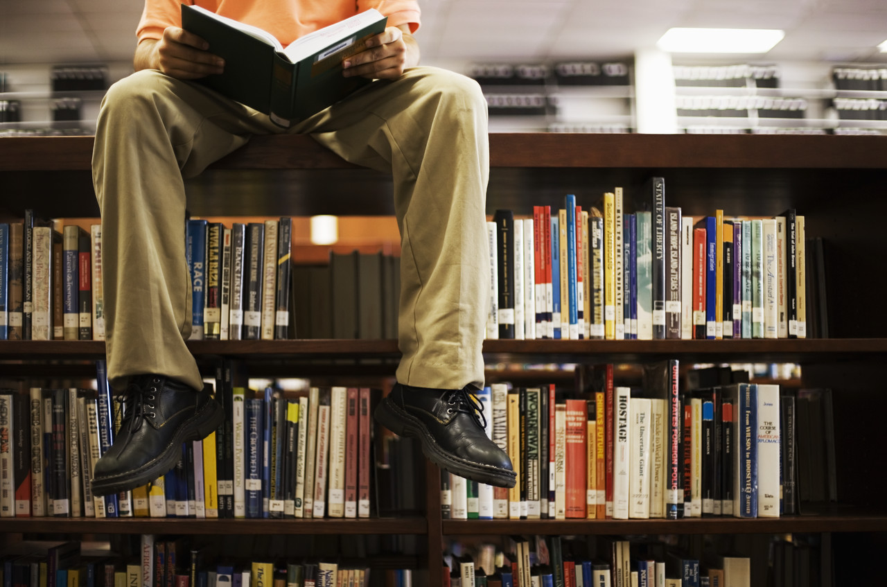 Man sitting on bookshelf with a book in his hands