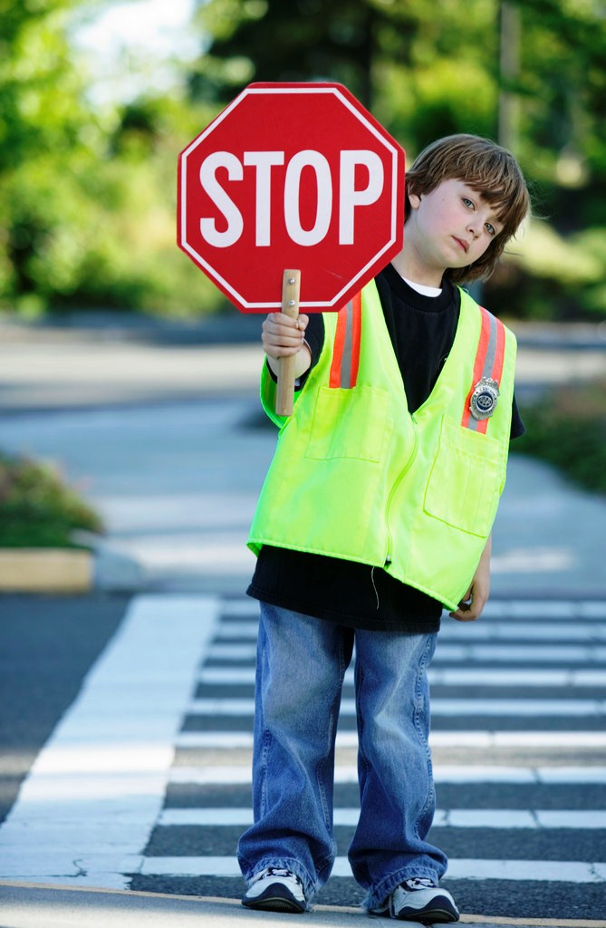 Young boy in the crosswalk wearing a crossing guard vest and holding a stop sign