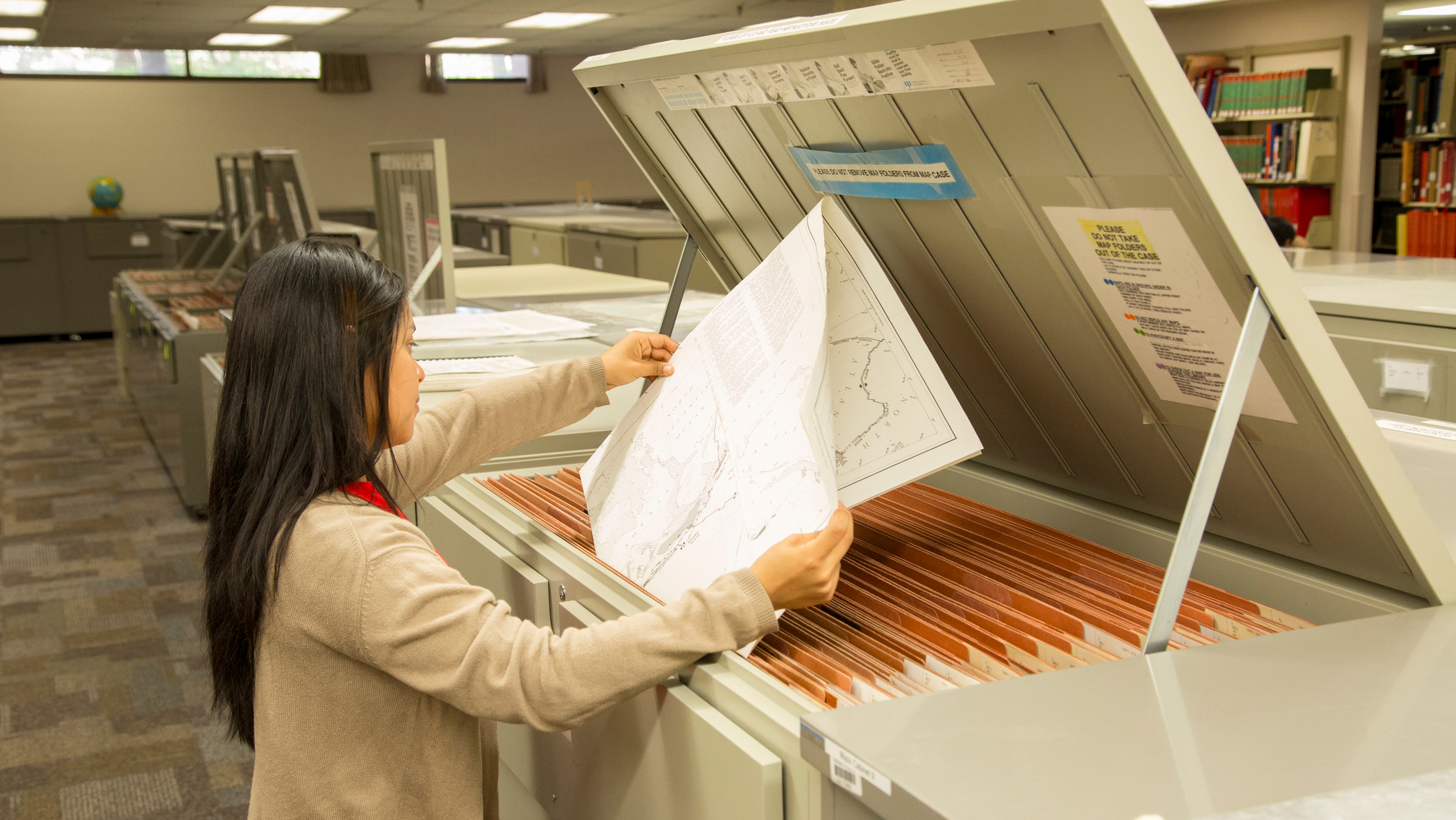 Student searching for maps in the print map collection