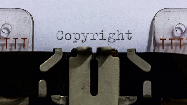 "decorative photo of a typewriter framing a piece of paper with the word ""copyright"""