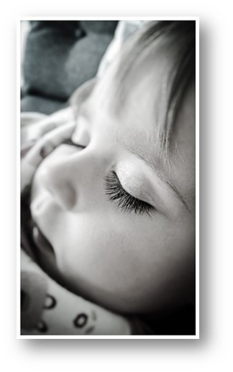 Black and white image of a sleeping child.