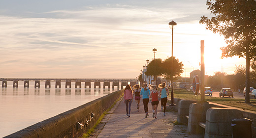 Photograph of people walking in the evening on Riverside, Dundee with the Tay Rail bridge in the background