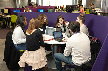 Students around a table studying with laptops in the Library Hub