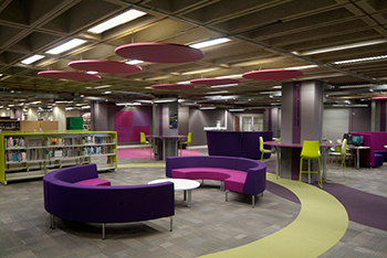 Photograph of the Library Hub with pink and purple couches and decor