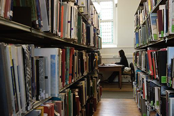 A photograph taken between bookshelves of a student studying in Richview Library. The Planning and Architecture Library