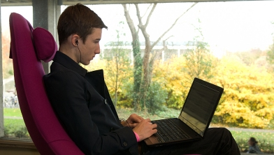 A student  on a laptop in a big comfortable pink chair by a window in the Library Hub