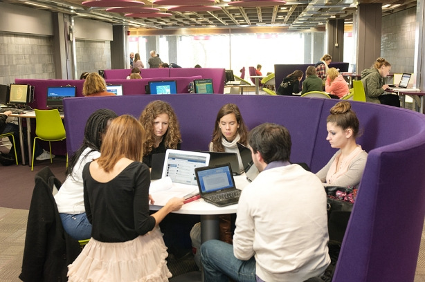 Students participating in group study in the Social Hub in James Joyce Library. They are sitting on purple couches