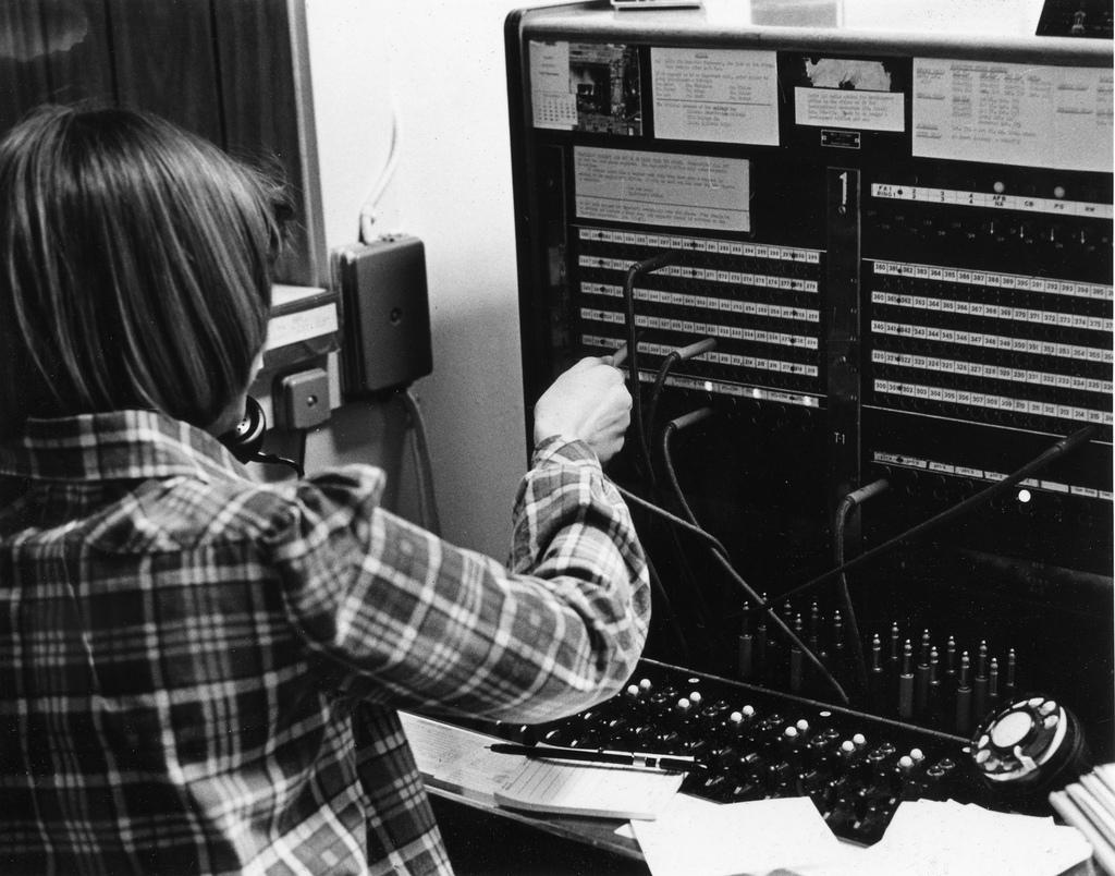 Black and white photograph of a woman working a circuit board