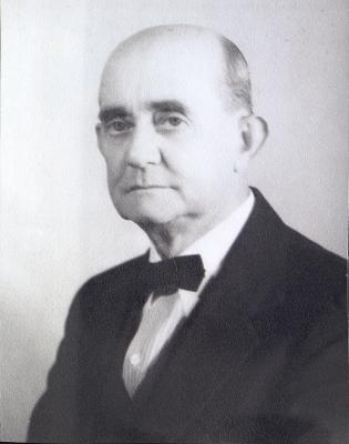 A black and white portrait photograph of an unsmiling, bald man wearing a black suit, white shirt and black bowtie.
