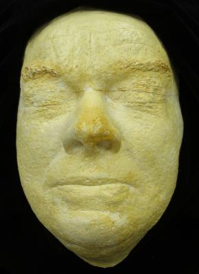 Yellowed plaster life mask, eye closed, set on black cloth background.