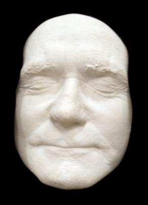White plaster life mask, eyes closed set on a black cloth background.