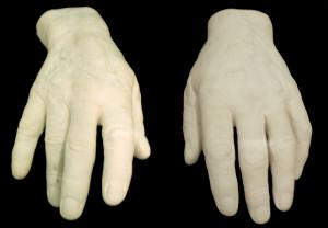 white plaster casts of a right and left hand, set on a black cloth background.