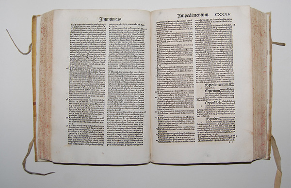 Large, rare book, opened to two page in the middle, each page has two columns of ancient Latin text.
