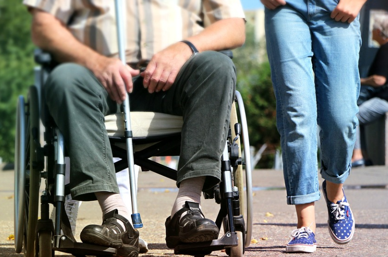 Photo of a wheelchair user and a pedestrian