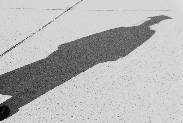 Shadow of a person wearing mortarboard and gown