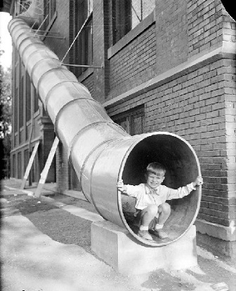 A boy is shown climbing down a fire escape on the side of a brick building.