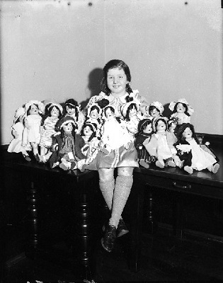 A girl sits surrounded by a dozen dolls.