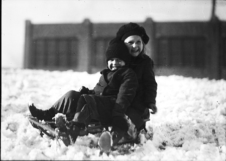 A boy and girl pose for a photograph  while sitting on a sled. They are surrounded by snow and dressed for the weather.