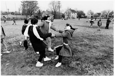 Three girls hold hands as they spin around in a circle. Other children play in the open field in the background.