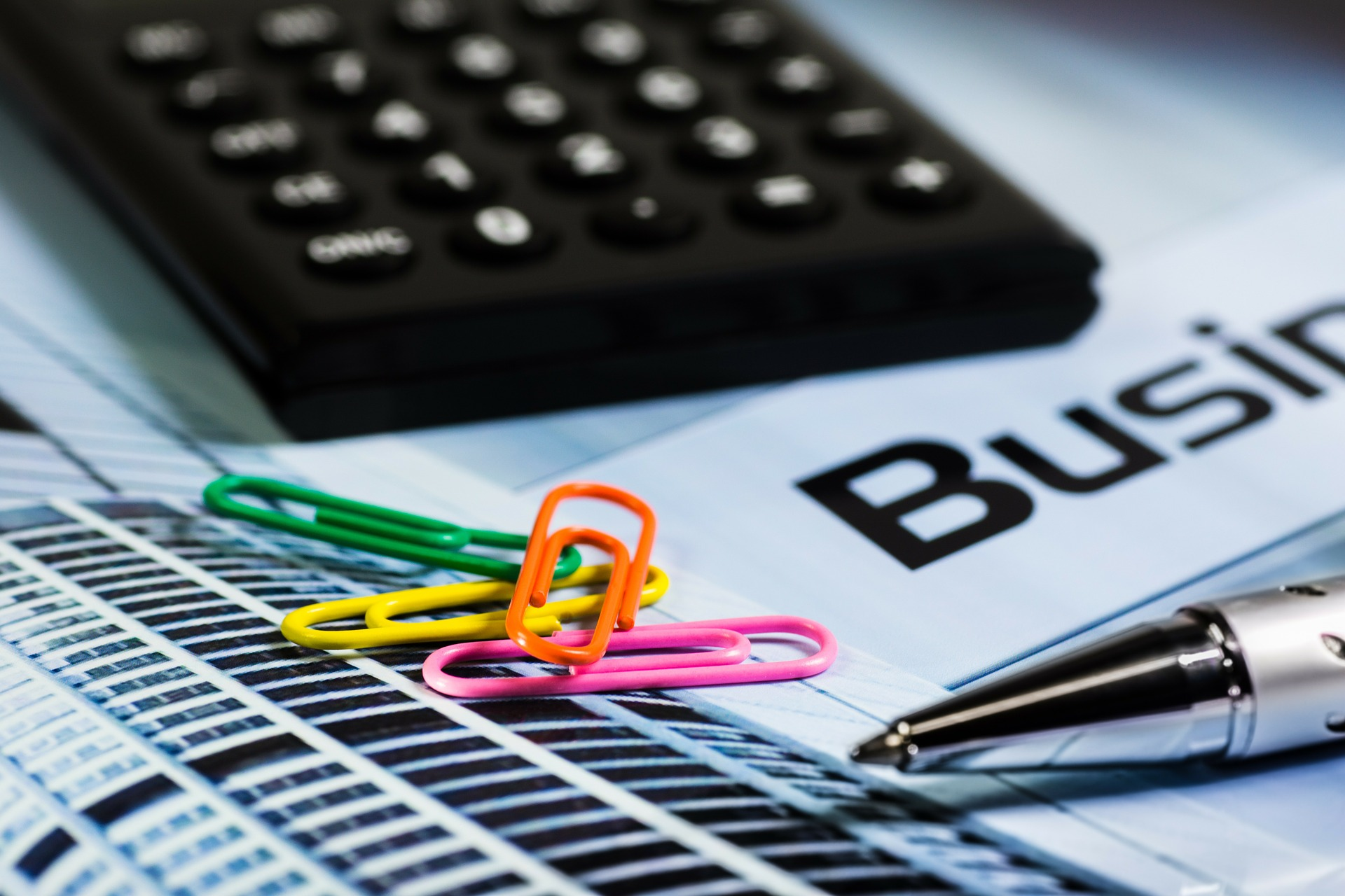 calculator and paper clips on a business magazine