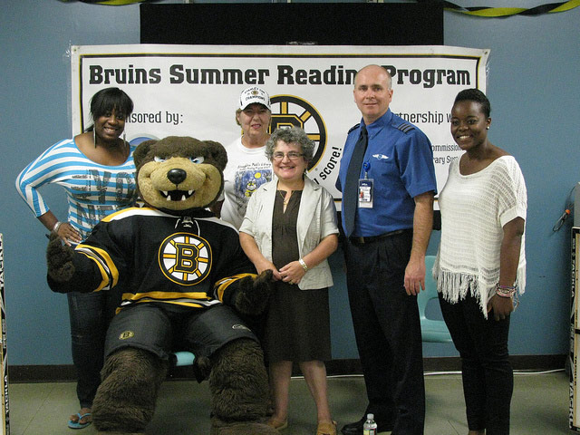 Bruins poses with library staff and community members in Stoughton, 2012